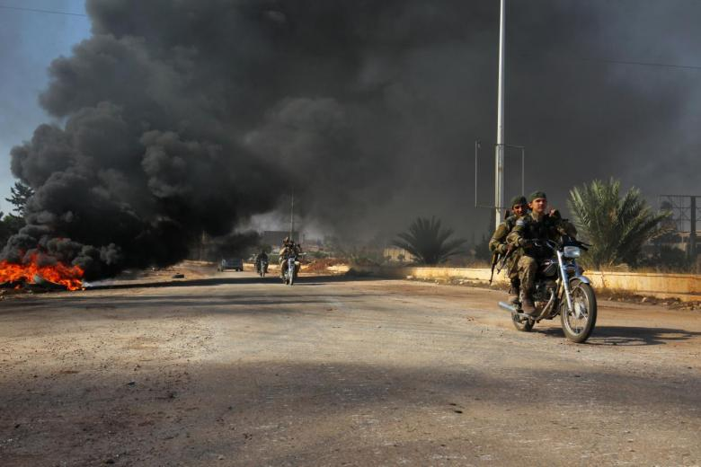 Rebel fighters drive their motorcycles under the smoke of burning tyres, western Aleppo city, Syria November 3, 2016. REUTERS/Ammar Abdullah